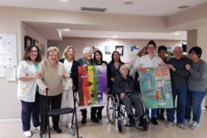 Personas mayores con los carteles ganadores del concurso